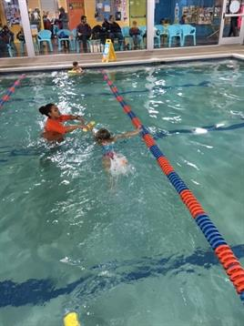 Swim instructor teaching her student