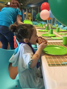 Little girl happily eating pizza