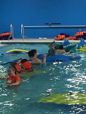 Swim instructors and students swimming in the pool