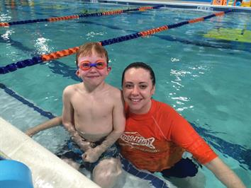 Swim instructor and her student smiling