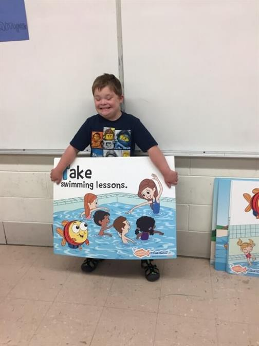 Student holds a Swimming Lessons poster