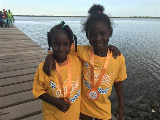 Two Students Wearing Their Medals From Goldfish Swim School