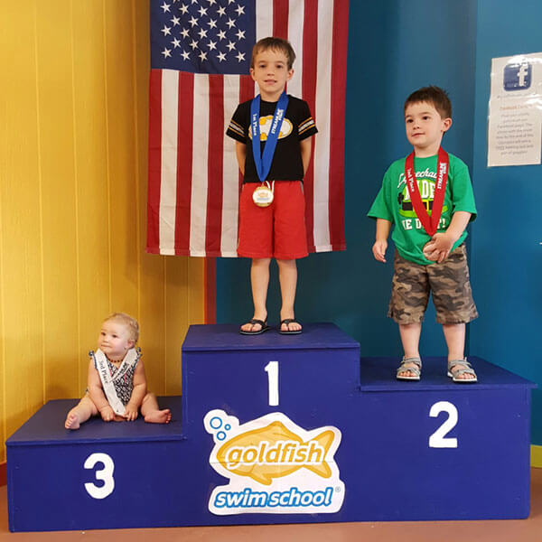 Three kids standing on the first, second, and third place podium