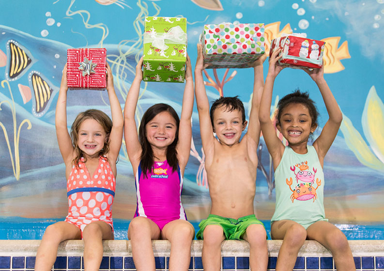 Four kids holding up presents