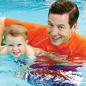 Instructor with little boy swimming
