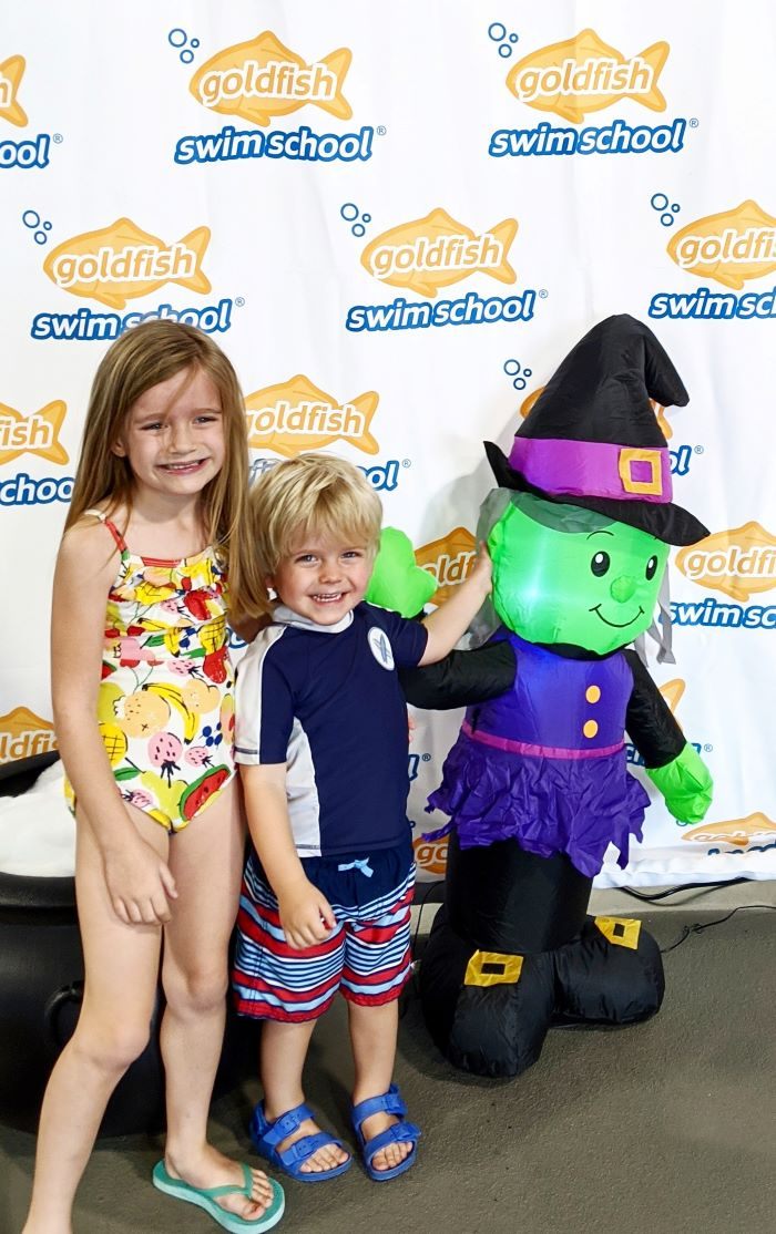 Children standing next to inflatable witch